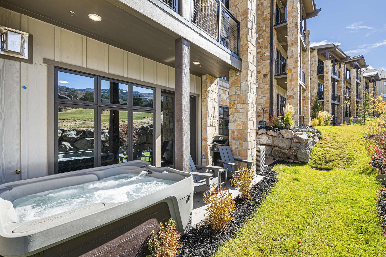 The patio windows reflect the golf course and mountain views