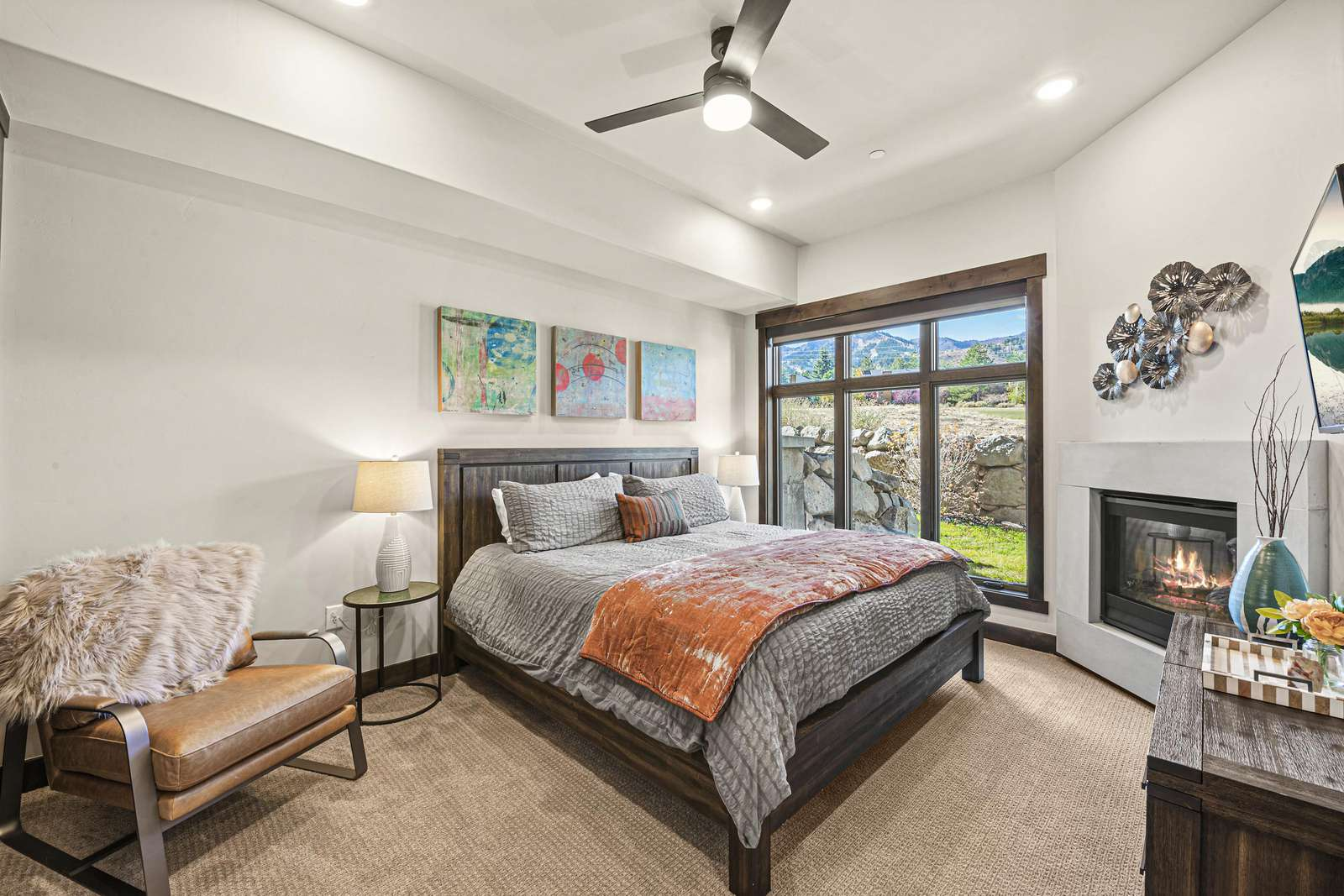 Stylistic master bedroom with TV and fireplace