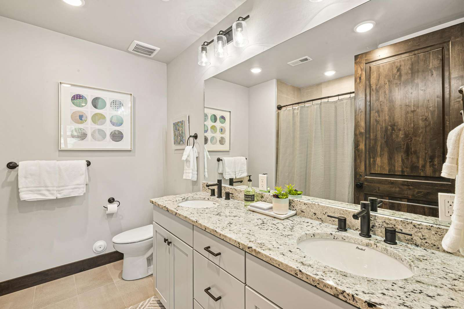 En suite bathroom (to guest bedroom) with double vanity and large bathtub and shower