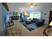 Spacious Living room with Sofa, Arm chairs, Flat screen TV Ceiling fan and remote Mini-Split A/C thumb