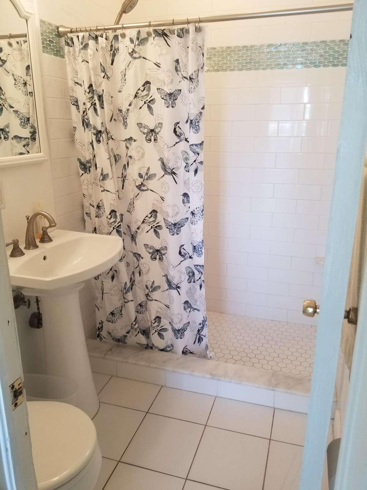Bath with shower is in the hallway between the 2 bedrooms