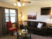Spacious living room with ceiling fan, lots of lighting, and more! thumb