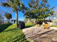 Large, fenced back yard with fire pit and gas grill thumb