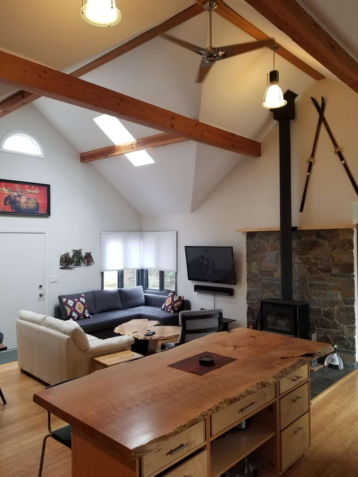 Living Area view from Kitchen.  Free Standing Wood Stove & Large TV
