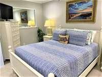 Queen bed in roomy open bedroom thumb
