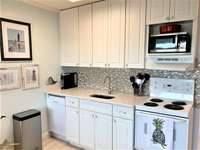 Full Kitchen with new white cabinets and tiled backsplash thumb