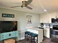 Newly renovated coastal kitchen with quartz countertops, backsplash and stainless appliances.  thumb