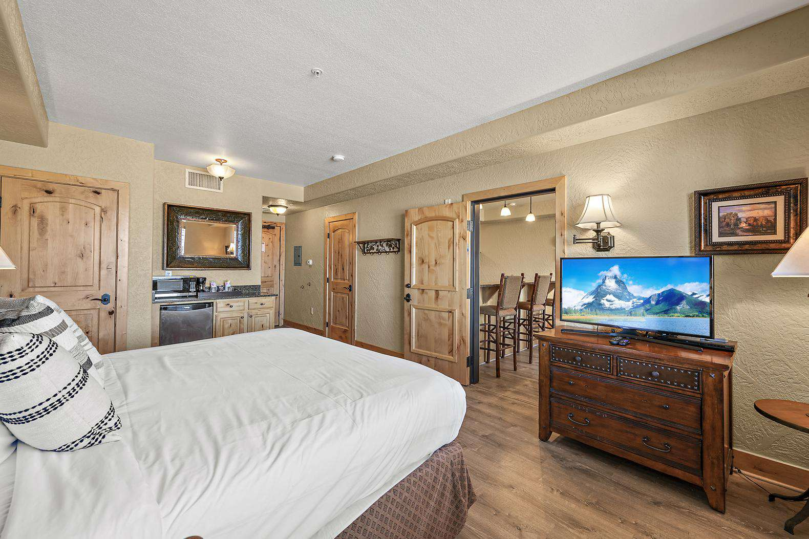 Spacious master bedroom with queen bed, tv, and dresser