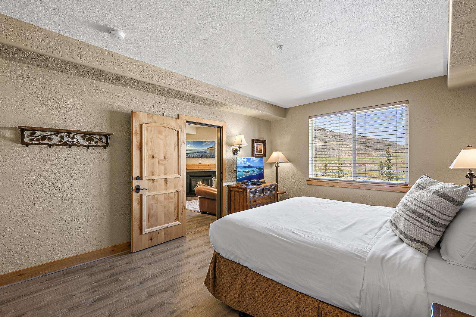Open bedroom with open private door looking into living room