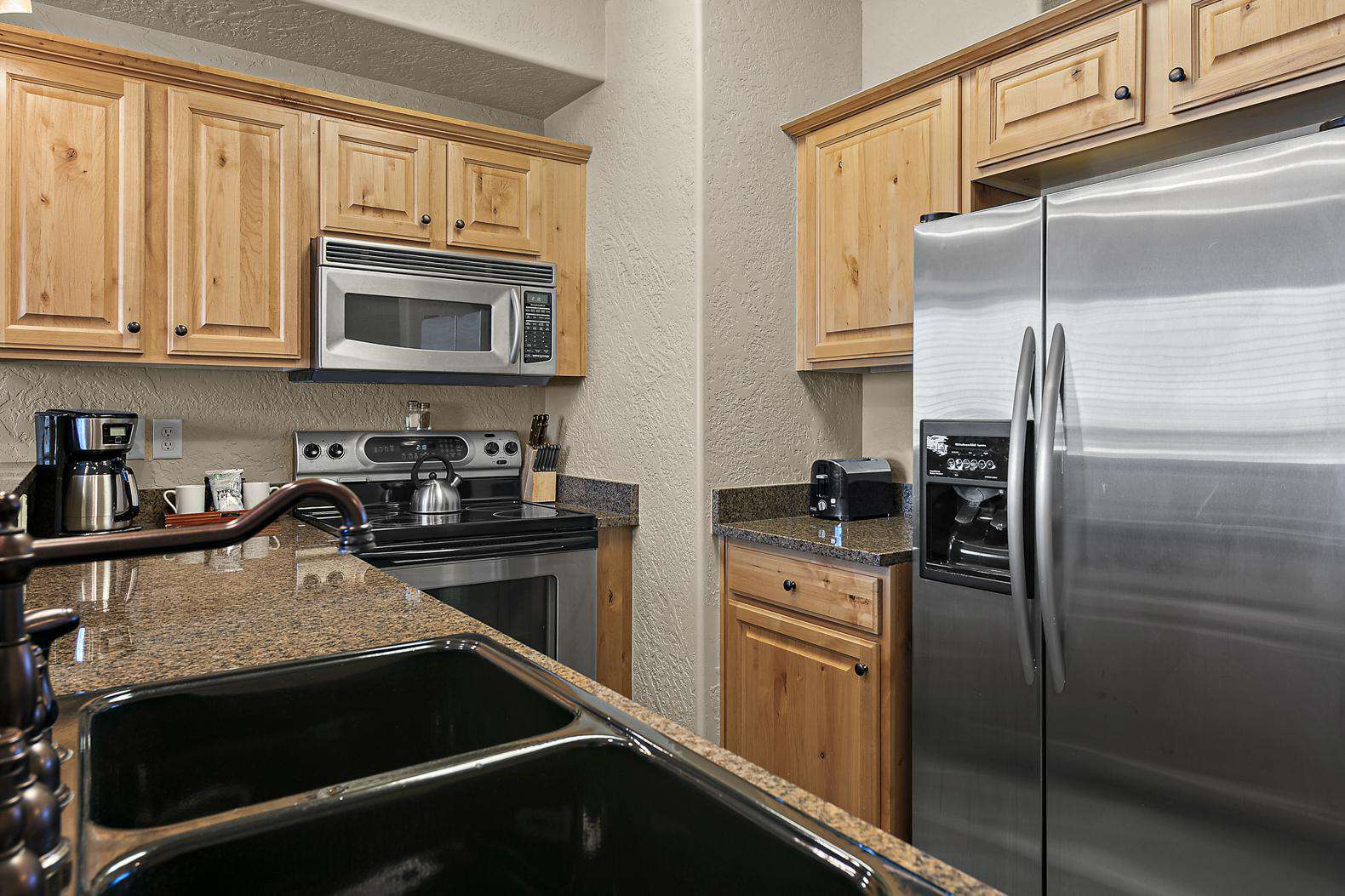 Quality kitchen with fridge/freezer, oven/range, microwave, and coffee maker