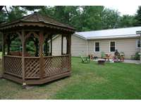 Back of cabin showing gazebo with glider thumb